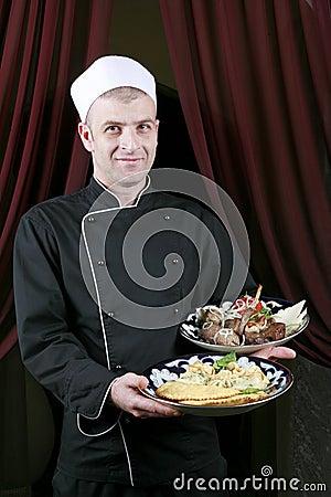 Portrait mid adult male chef in kitchen present