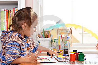 Baby draws paints at the table