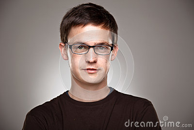 Portrait of a normal boy with rimmed glasses on a grey background