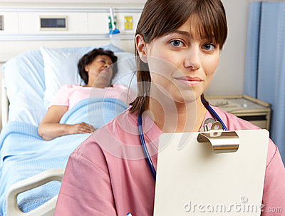 Portrait Of Nurse With Patient In Background