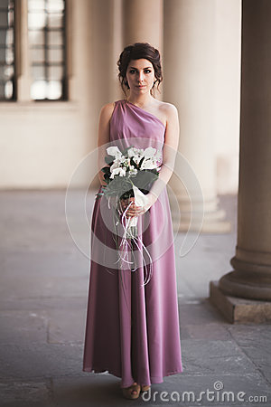 Free Portrait Of A Beautiful Young Bride That Stands Between The Columns Near Old Building And Holding Bridal Bouquet Stock Photo - 77654940