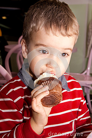 Free Portrait Of A Little Boy Eating Tasty Cocoa Muffin With Whipped Topping Stock Images - 66531774