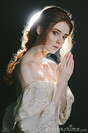 Free Portrait Of A Praying Young Red-haired Woman In Vintage Ash Dress With Open Shoulders On A Black Background In Backlight. A Prince Stock Images - 115798134