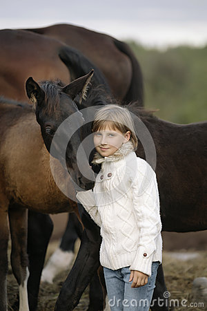 Free Portrait Of A Young Happy Little Girl In White Sweater And Jeans With Foal. Lifestyle Royalty Free Stock Images - 78013249