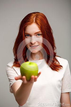 Free Portrait Of Beautiful Ginger Girl Holding Apple Blurred Over Gray Background. Royalty Free Stock Photo - 73930865