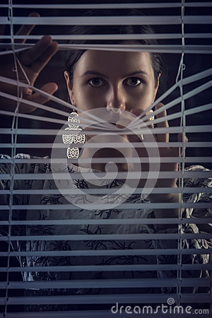 Free Portrait Of Beautiful Mysterious Woman Looking Through Jalousie,louver Royalty Free Stock Photography - 34769577