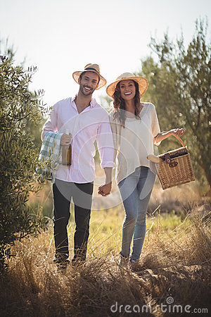 Free Portrait Of Happy Young Couple Carrying Picnic Basket Royalty Free Stock Photo - 93964515