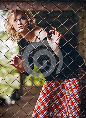 Free Portrait Of Lovely Grunge Rock Girl In Checkered Skirt And Sweater Standing Behind Metallic Grid Stock Images - 92741604