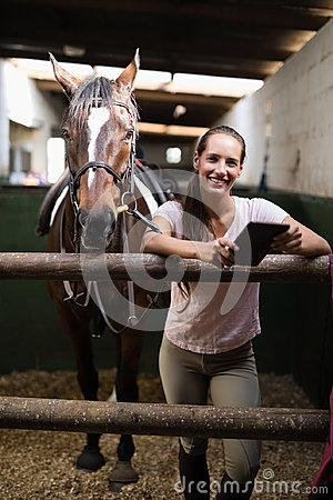 Free Portrait Of Smiling Female Jockey Using Digital Tablet By Standing By Horse Royalty Free Stock Photo - 97407435