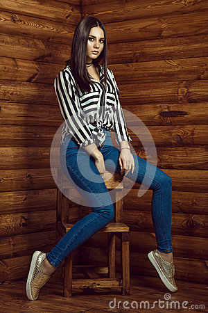 Free Portrait Of Young Beautiful Dark-haired Model Wearing Skinny High-waisted Jeans, Striped Shirt, Choker And Golden Sneakers Royalty Free Stock Photos - 85150588
