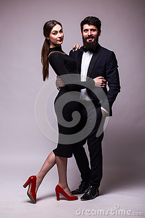 Free Portrait Of Young Couple In Love Posing Dressed In Classic Clothes On Grey Backround. Man With Beard In Suit, Woman In Black Dress Stock Images - 67786514