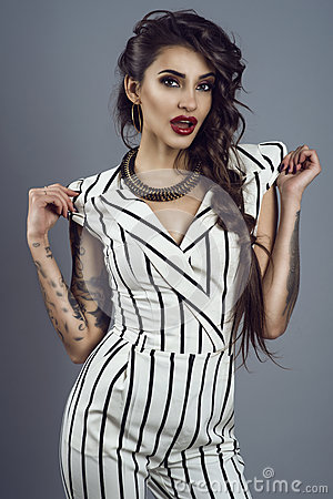 Free Portrait Of Young Gorgeous Dark-haired Tattooed Lady In Striped Overall And Splendid Necklace Holding Sleeves In Her Hands Royalty Free Stock Photography - 85055807
