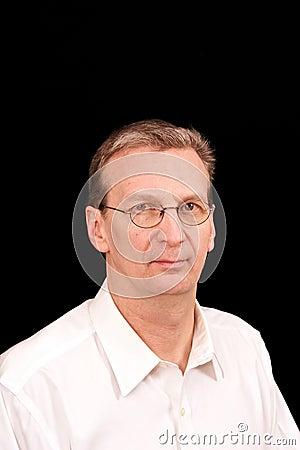 Portrait of older man on black in white shirt