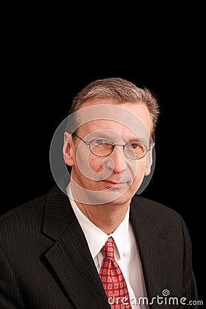 Portrait of older man in suit against black