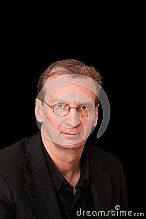 Portrait of older serious man on black