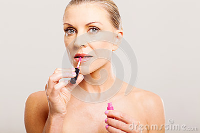 Older woman putting lip gloss