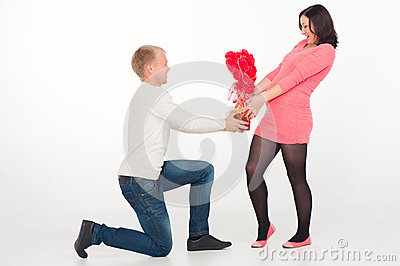 Portrait of a pregnant woman and her husband with flowers