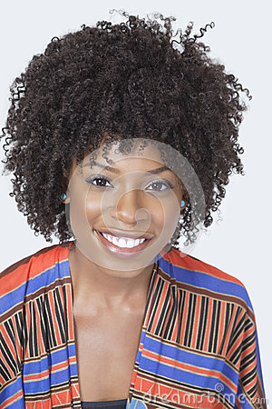 Portrait of pretty African American woman in traditional wear smiling over gray background