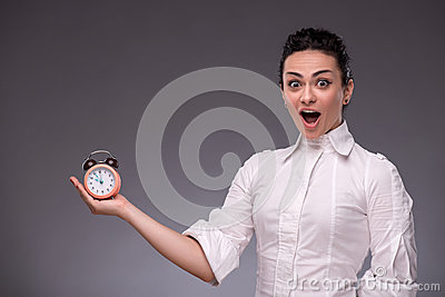 Portrait of pretty girl holding an alarm clock in
