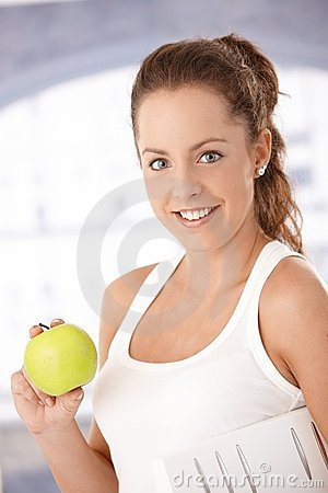 Portrait of pretty girl holding an apple smiling