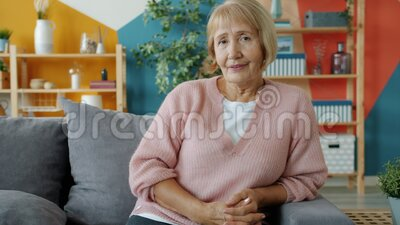 Portrait of pretty senior lady in casual clothing sitting on couch at home smiling. Looking at camera. Positive emotions and retired people concept stock footage