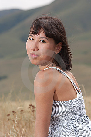 Portrait of a pretty young lady on a meadow hills