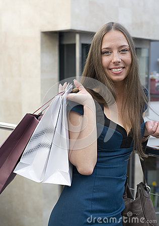Portrait of pretty young woman with bags in the shop
