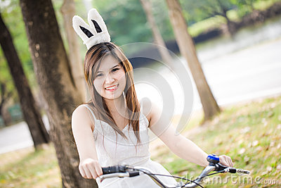 Portrait of pretty young woman with bicycle in a park smiling