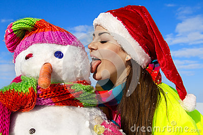 Portrait of a pretty young woman kissing a snowman