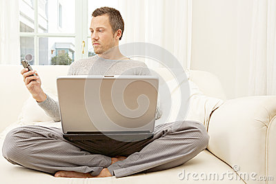 Portrait of professional man with laptop and smart phone at home.
