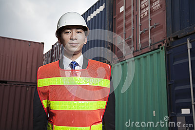 Portrait of proud engineer in protective workwear standing in a shipping yard Stock Photo