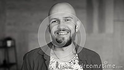 Portrait rapproché d'un jeune homme chauve et attrayant à la barbe vidéo en noir et blanc clips vidéos