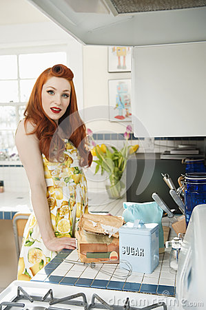 Portrait of a redheaded woman standing by the kitchen counter