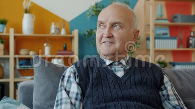 Portrait of retired man in casual clothing sitting on couch at home smiling. Slow motion portrait of good-looking retired man in casual clothing sitting on couch stock video