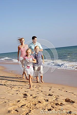 Portrait Of Running Family On Beach