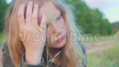 Portrait of sad blonde girl 11 years old. Pensively and dreamily looks at the blade of grass. Portrait of the young blonde girl 11 years old. Pensively and stock video