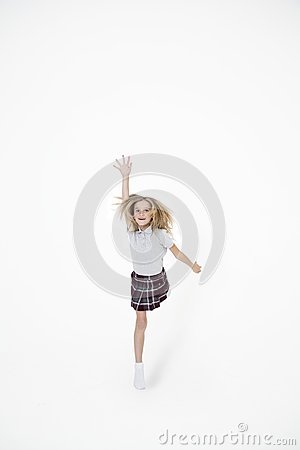 Portrait of school girl jumping with hand raised over white background