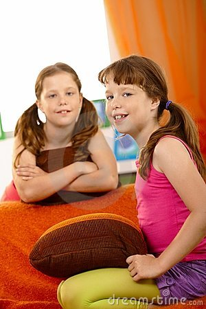 Portrait of schoolgirl on couch with friend