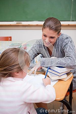 Portrait of a schoolgirl writing with her teacher