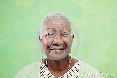 Portrait of senior black woman smiling at camera on green background Stock Photo
