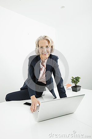 Portrait of senior businesswoman with laptop sitting on desk in office