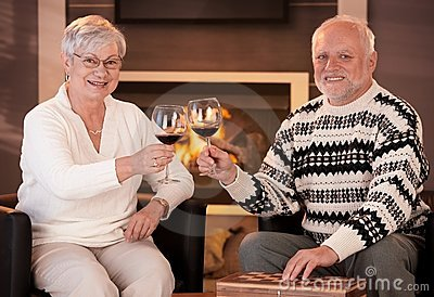 Portrait of senior couple clinking wine glasses