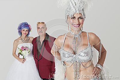 Portrait of senior showgirl with father and daughter in wedding dress in background