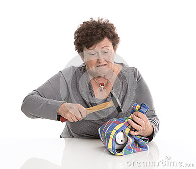 Portrait: senior woman smashing her piggy box. Isolated over whi
