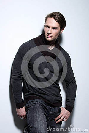 Portrait of sexy handsome man in gray pullover.