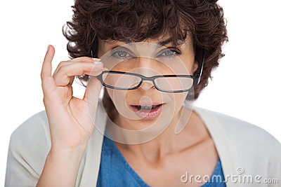 Portrait of a shocked woman looking over her glasses