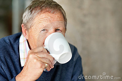 Portrait of smart old man drinking cup of coffee