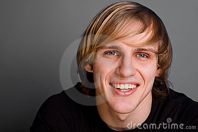 Portrait of smiling blond man over gray background