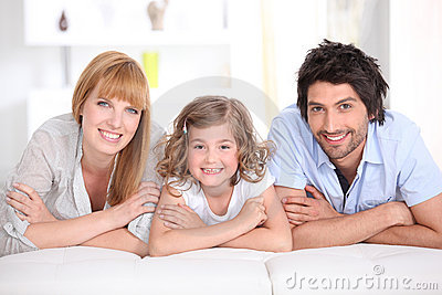 Portrait of a smiling family laid on a bed
