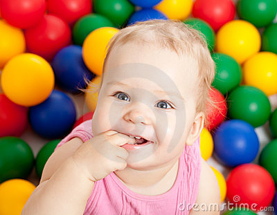 Portrait of a smiling infant among colorful balls